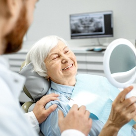 A dentist showing an older female patient her new smile after having her restoration placed