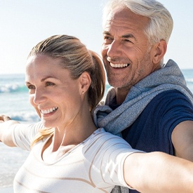 A middle-aged couple on the beach and smiling with their arms extend out to their sides