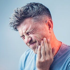Grimacing man holding jaw in pain